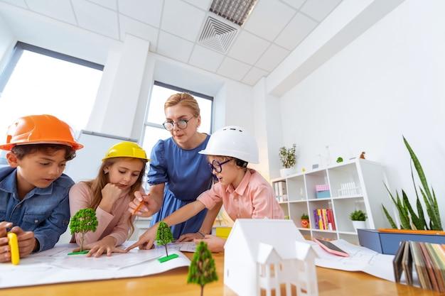 Professor com alunos. professora de óculos modelando cidade inteligente com seus jovens alunos enquanto estudava construção