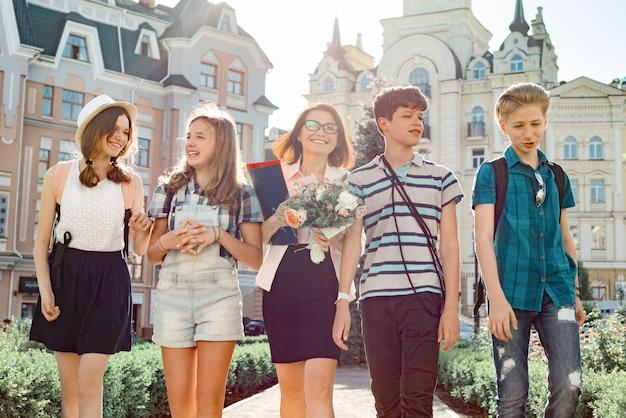 Professor com buquê de flores e grupo de crianças em idade escolar