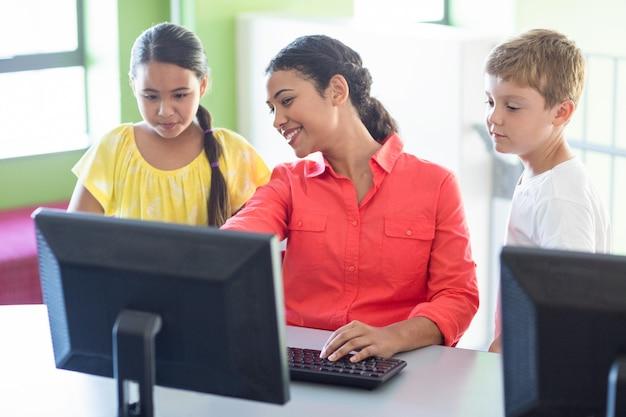 Professor com crianças na aula de informática