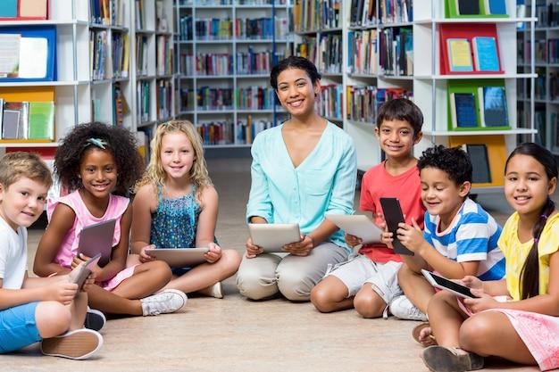Professor com crianças segurando tablets digitais