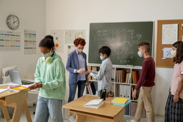Professor com desinfetante borrifando nas mãos de alunos em sala de aula