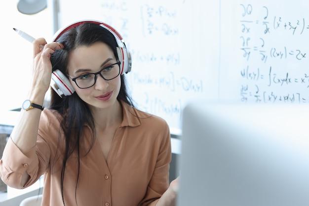 Professor com fones de ouvido na cabeça olhando para a tela do laptop
