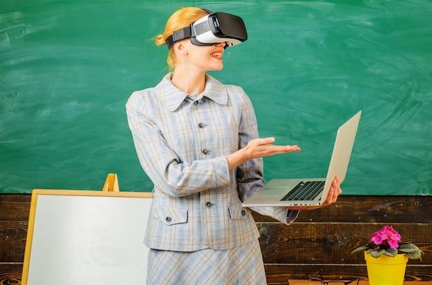 Professor com laptop em fone de ouvido vr. tecnologias modernas na escola inteligente. educação digital. tutor sorridente em sala de aula.