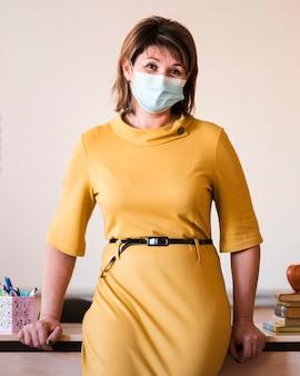 Professor com máscara em pé