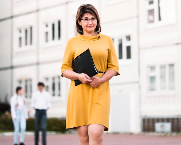Professor com notebook ao ar livre