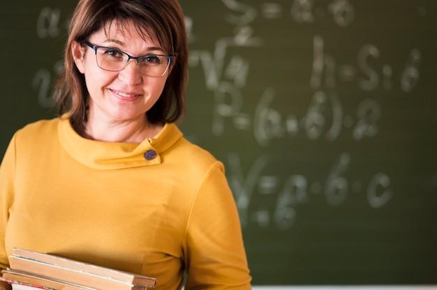 Professor com pilha de livros na sala