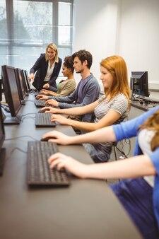 Professor computador, ajudando, um, bonito, estudante, em, dela, classe