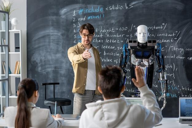 Professor contemporâneo apontando para um dos alunos querendo fazer perguntas sobre as características do robô parado perto do quadro-negro