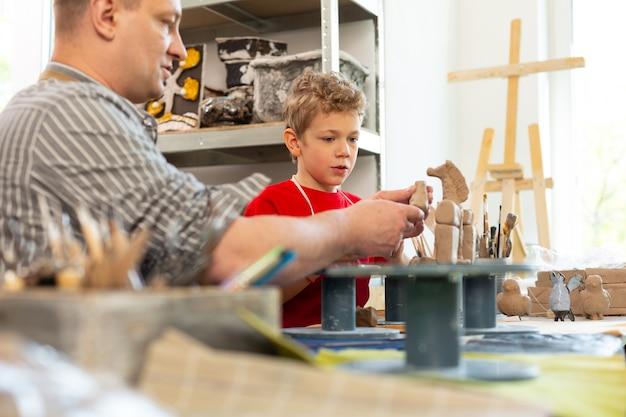 Professor conversando com seu talentoso aluno esculpindo figuras de argila