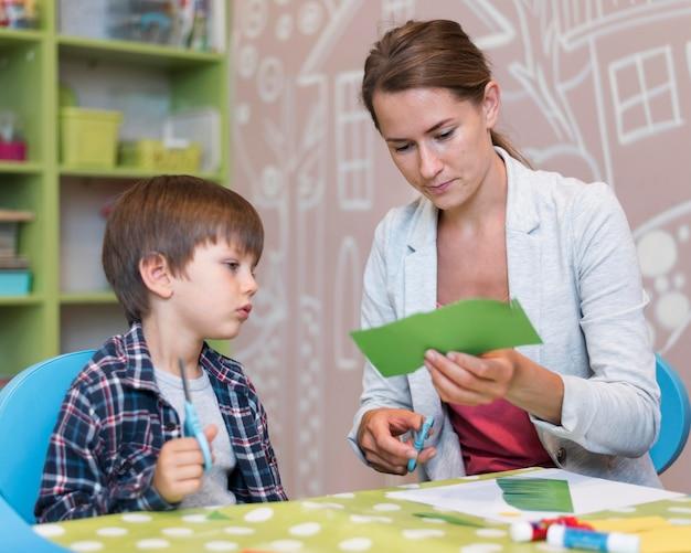 Professor cortando papel para menino