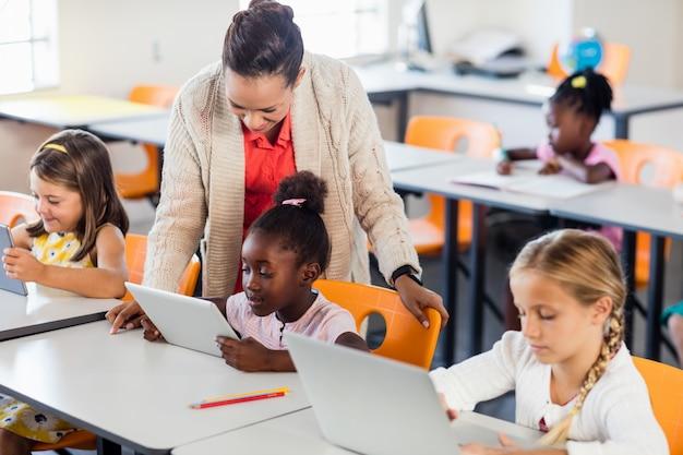 Professor dando aula para seus alunos com laptops