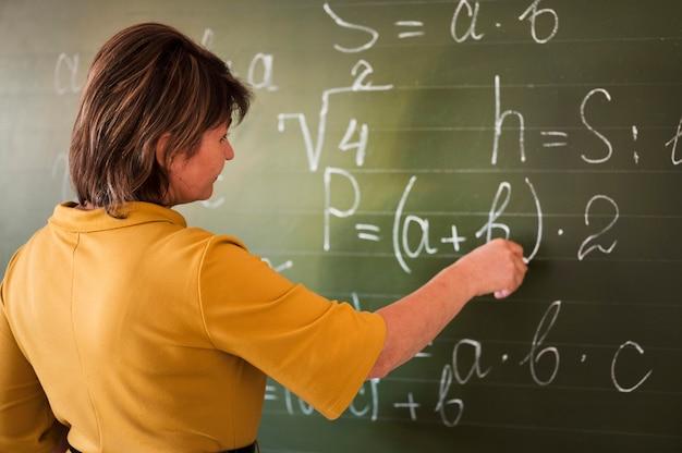 Professor de alto ângulo escrevendo no quadro-negro