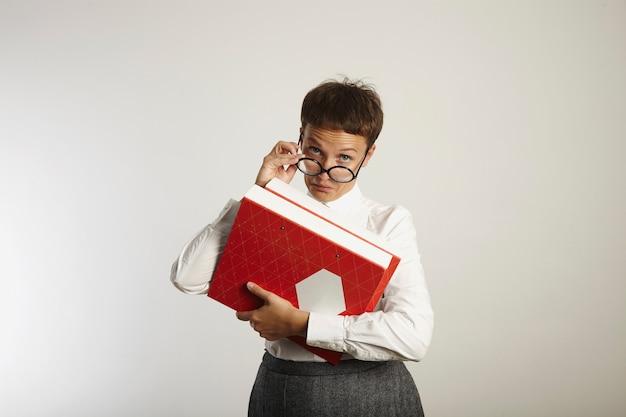 Professor de aparência severa em blusa branca, camisa de tweed cinza e óculos pretos redondos segurando uma pasta vermelha e branca brilhante parece suspeito acima dos óculos e faz uma cara cética