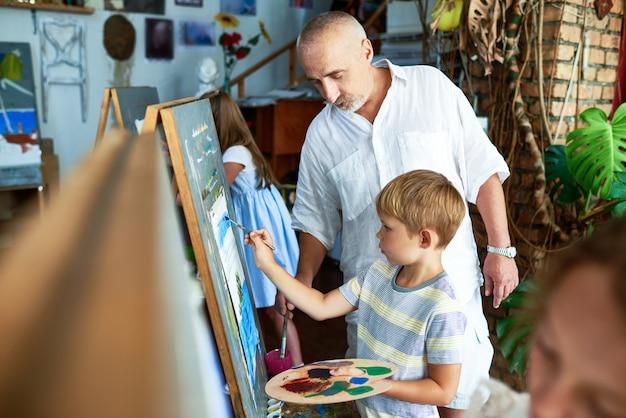 Professor de arte, ajudando o menino