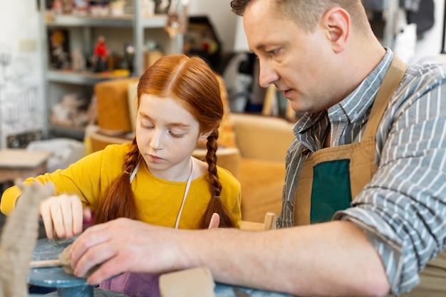 Professor de arte auxiliando seu atraente aluno ruivo