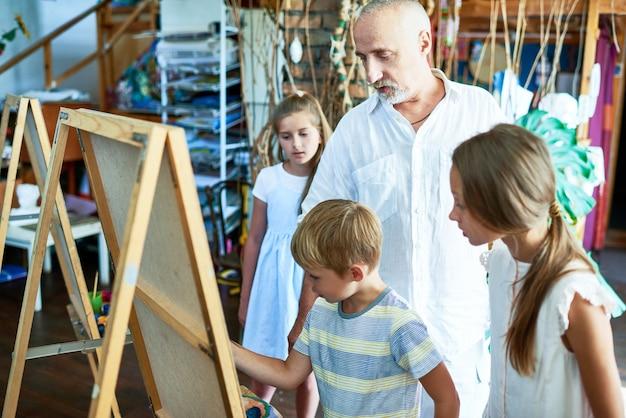 Professor de arte madura trabalhando com crianças