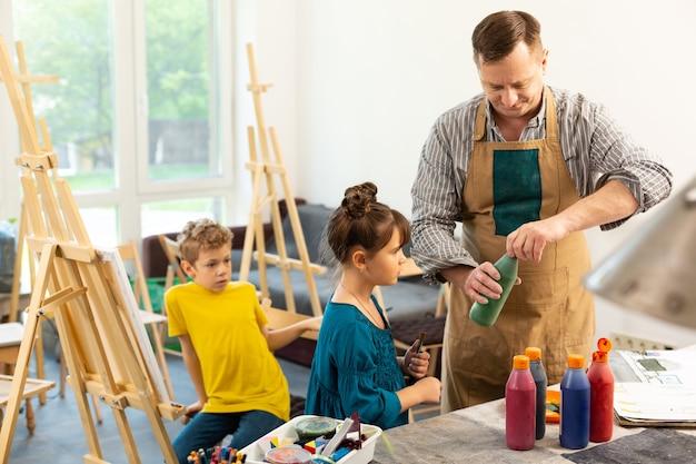 Professor de arte usando tintas de abertura de uniforme para crianças