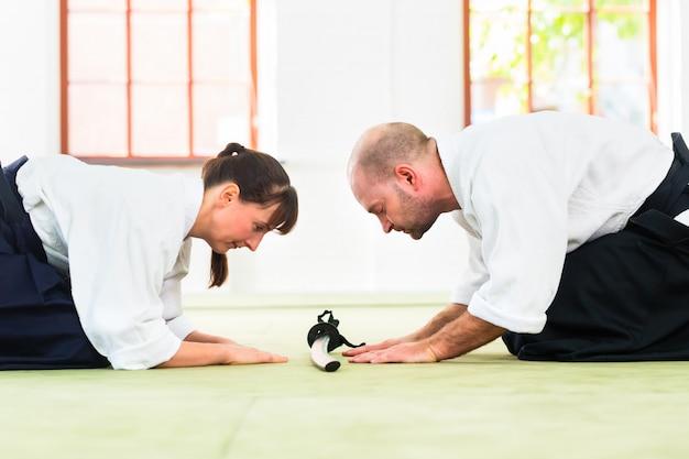 Professor de artes marciais de aikido e estudante fazer um arco