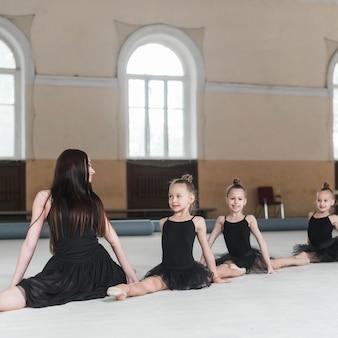 Professor de bailarina olhando para três meninas, estendendo-se no chão