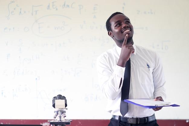 Professor de ciências africano que ensina e que pensa na sala de aula com microscópio.