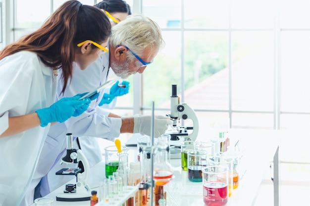 Professor de ciências e equipe de estudantes que trabalham com produtos químicos no laboratório