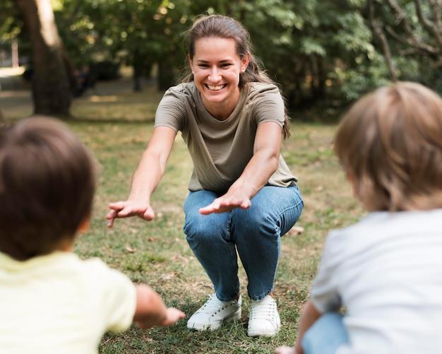 Professor de close-up e crianças se exercitando ao ar livre