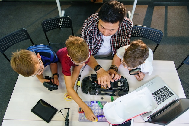 Professor de engenheiro eletrônico com jovens estudantes europeus trabalhando em conjunto com um modelo de carro controlado por rádio. solda de fios e circuitos, experimentos físicos.