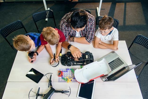 Professor de engenheiro eletrônico com jovens estudantes europeus trabalhando em conjunto com um modelo de carro controlado por rádio.