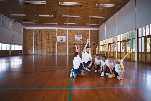Professor de esportes e crianças da escola brincando na quadra de basquete