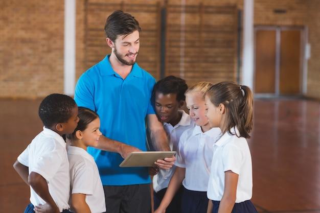 Professor de esportes e crianças da escola usando tablet digital na quadra de basquete