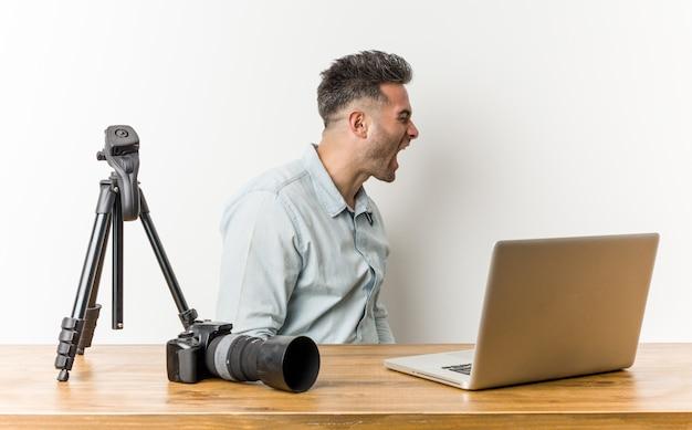 Professor de fotografia bonito jovem gritando para um espaço de cópia