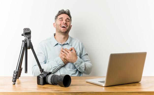 Professor de fotografia bonito jovem rindo mantendo as mãos no coração, o conceito de felicidade.