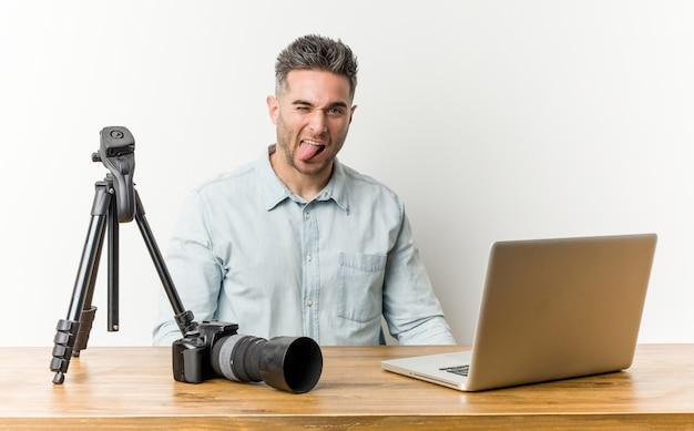 Professor de fotografia jovem bonito engraçado e amigável saindo da língua