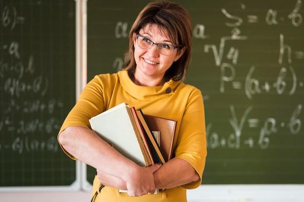 Professor de frente com pilha de livros