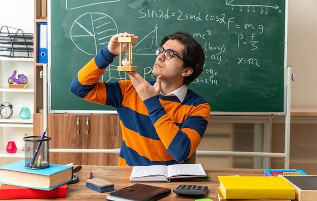 Professor de geometria jovem sério caucasiano usando óculos, sentado na mesa com as ferramentas da escola, segurando uma ampulheta verticalmente olhando para ela
