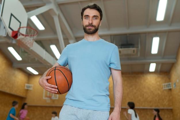 Professor de ginástica de tiro médio segurando uma bola de basquete