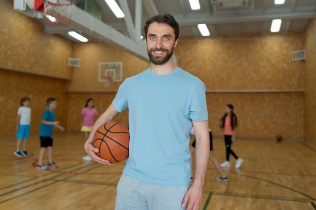 Professor de ginástica de tiro médio segurando uma bola