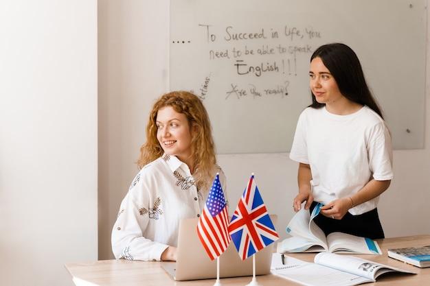 Professor de inglês pergunta a aluno na classe de brancos