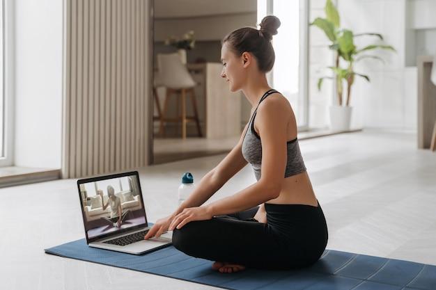 Professor de ioga conduzindo aula de ioga virtual em casa em uma videoconferência.