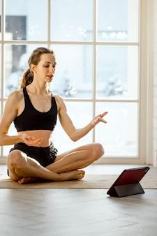 Professor de ioga dando aula de ioga virtual em casa em uma videoconferência