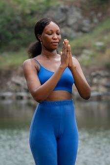 Professor de ioga praticando ao ar livre