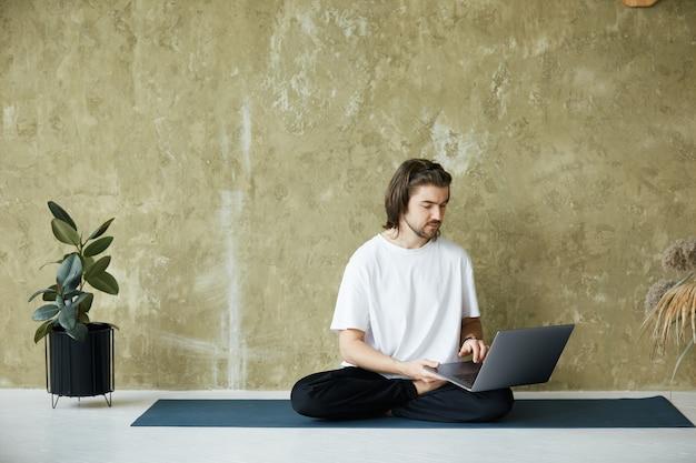 Professor de ioga usando laptop sentado em posição de lótus, prática de mediação remotamente, cópia espaço, conceito de saúde mental