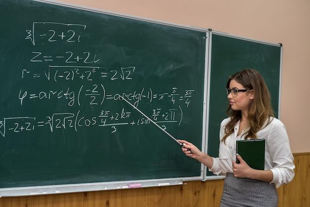 Professor de linda mulher caucasiana em pé na sala de aula perto do quadro-negro. educação. escola