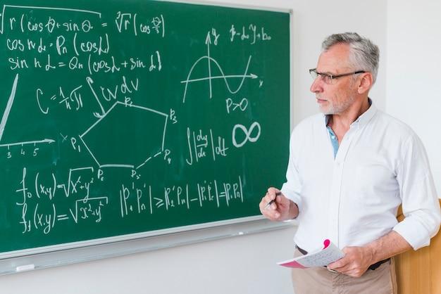 Professor de matemática envelhecido ao lado do quadro-negro