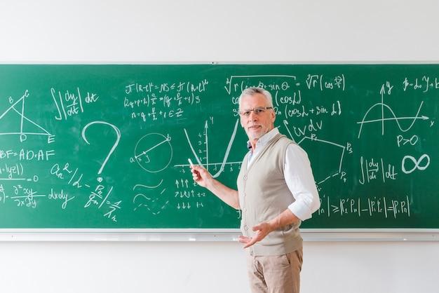 Professor de matemática envelhecido apontando com giz no quadro-negro