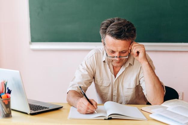 Professor de meia-idade nos óculos escrevendo atentamente.