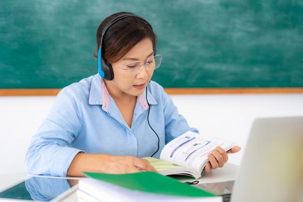 Professor de mulher asiática, lendo um livro alto para o aluno via e-learning de videoconferência no laptop
