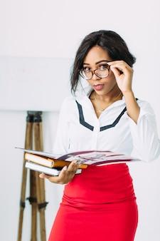 Professor de mulher jovem e bonita africano sorridente na camisa branca e saia vermelha, segurando livros e documentos