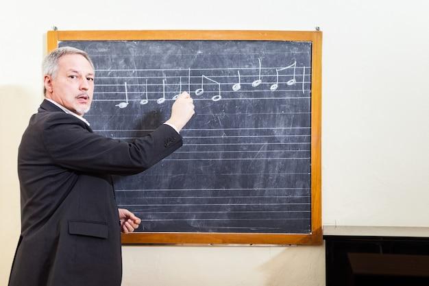 Professor de música, escrevendo em um quadro negro