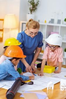 Professor de óculos. professor de óculos ensinando alunos a fazerem esboços para modelagem de casas na aula